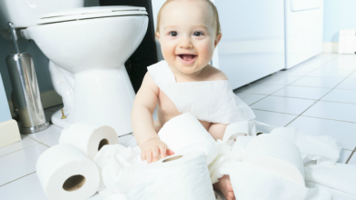 An older baby playing in the bathroom with rolls of toilet paper