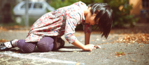 child drawing alone on the sidewalk