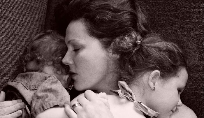 Sleeping mother holding two sleeping childeren