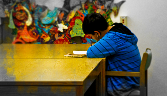 child sitting at a table doing homework