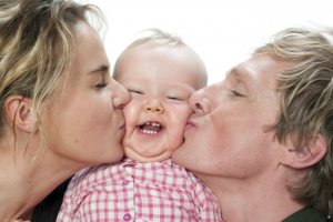 Mom and Dad kissing a babies cheeks
