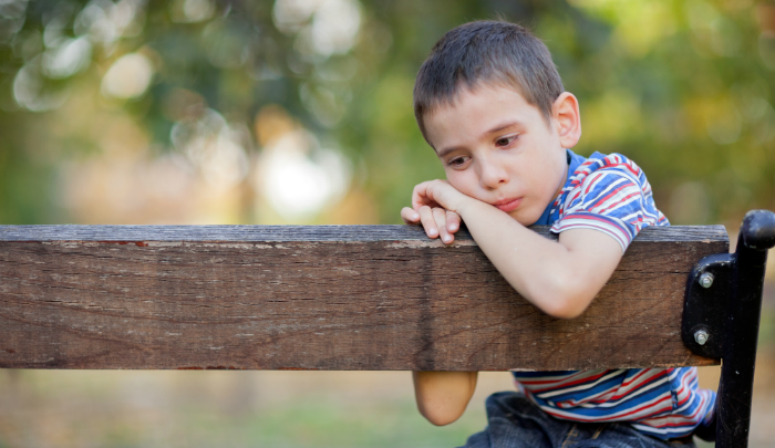 boy sitting on a wooden bench looking sad: parents, are you there but not really there?
