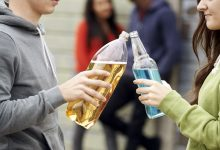Two teenagers toasting and about to drink alcohol