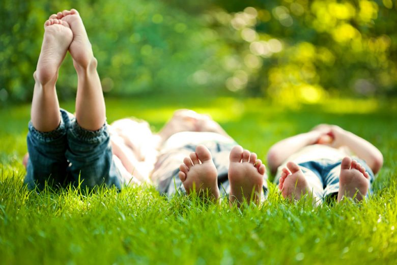 Three children lying on the grass looking up at the sky