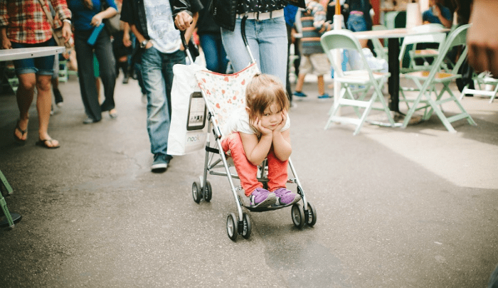 Girl toddler looking bored in stroller: how to discipline your kids less in public