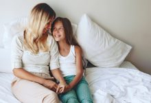 Mother and Daughter sitting on the bed together talking and smiling