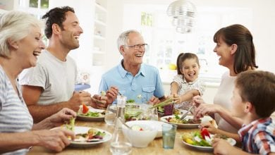 Grandparents, Parents, and Children sitting around the dinner table having a happy family meal