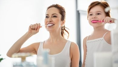 Mother and daughter looking in mirror brushing teeth
