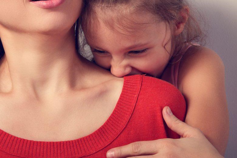 Child biting her mother's shoulder