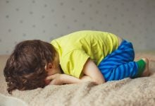Young child crying on his bed