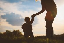 Silhouette of parent holding toddler's hand