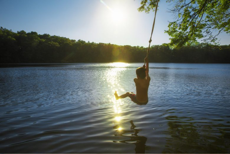 Boy on a rope swing over a lake