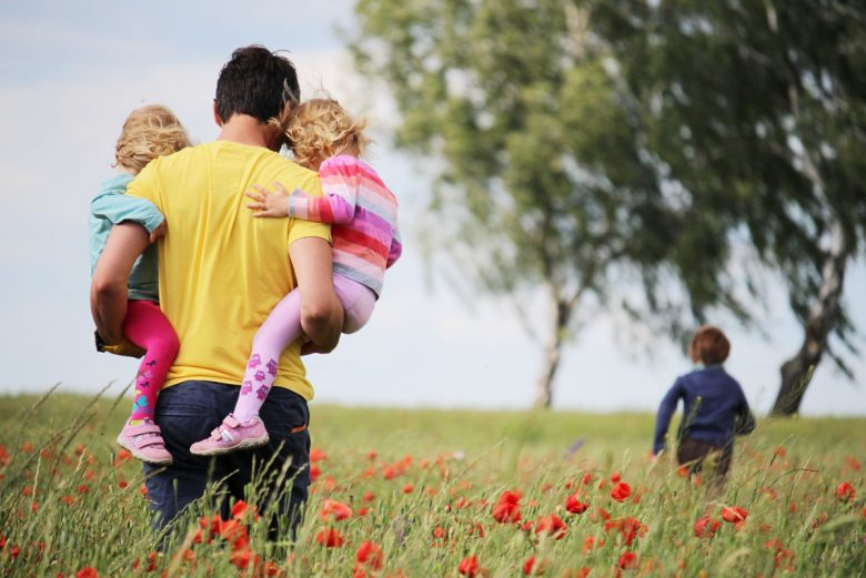 Father in a meadow holding two children while following another child toward a tree