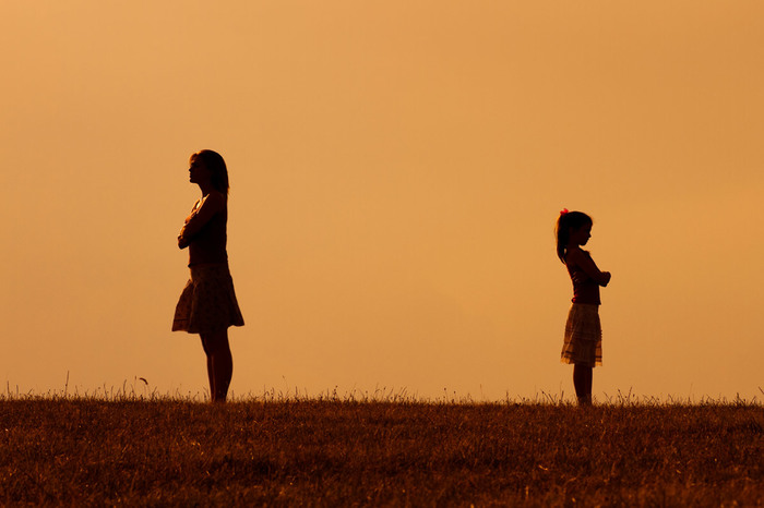 girl and woman standing apart from each other