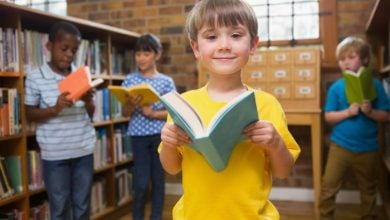 smiling boy holding an open book