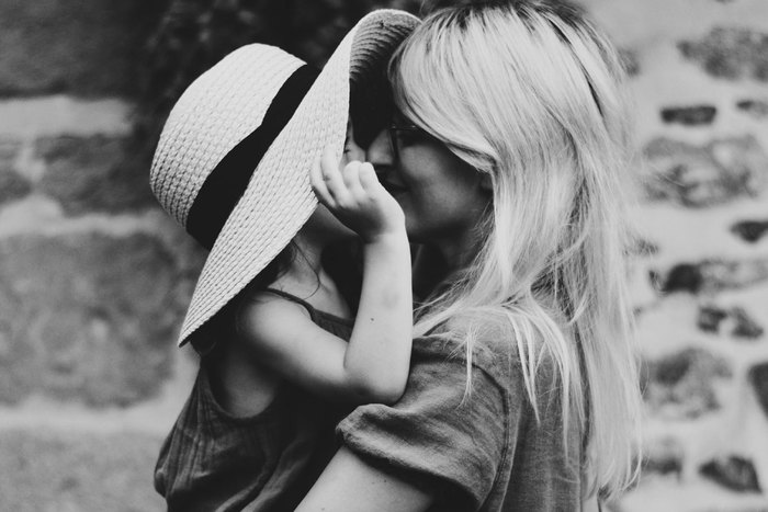 girl peeking out from a hat to kiss her mother