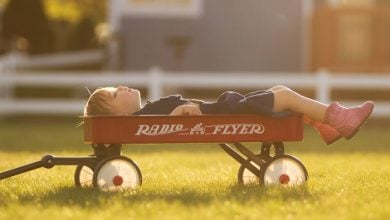 girl sitting in wagon looking at sky
