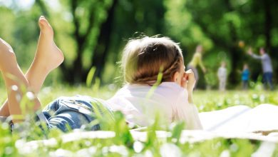 Child laying in a field reading a book while the family plays with a ball in the backgroud