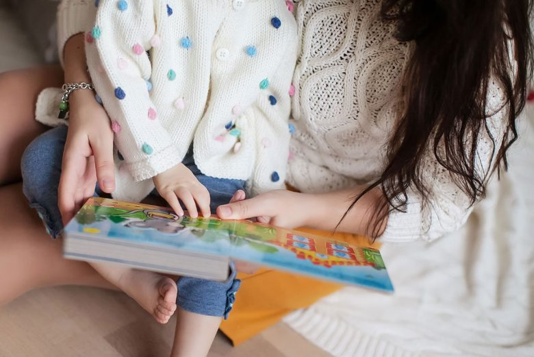 child sitting on mother's lap reading a book