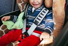 Child crying at being buckled into carseat