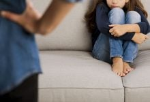 Child sitting on a couch timidly, while parent stands by them with hands on their hips.