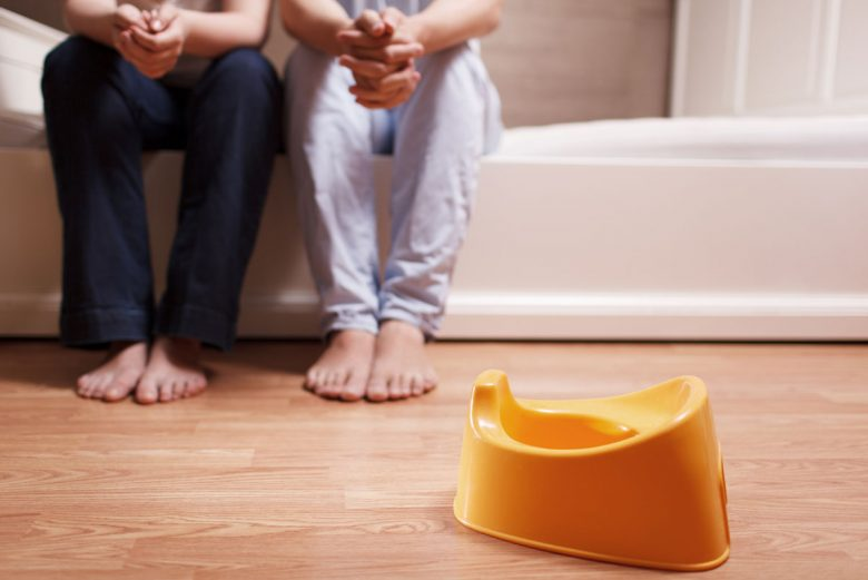 Parent and Child looking at a potty training potty