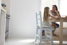 Parent and child talking at kitchen table