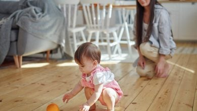 A toddler picking up an orange from the floor while the mother watches