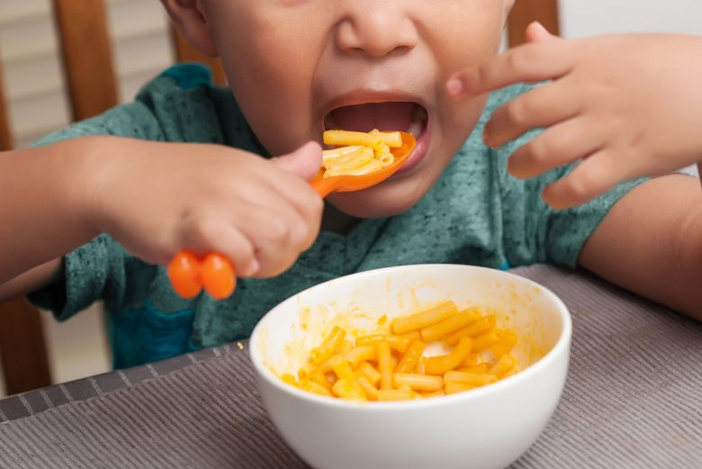 Child eating a big bite of mac and cheese