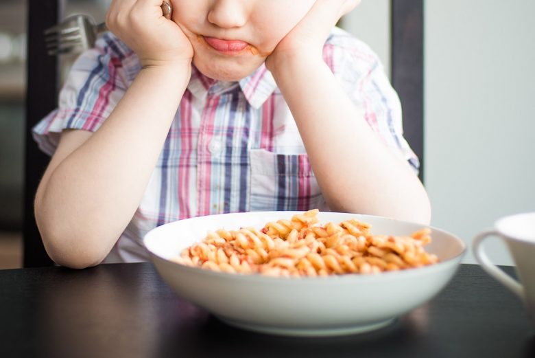 Little boy looking at his bowl of noodles